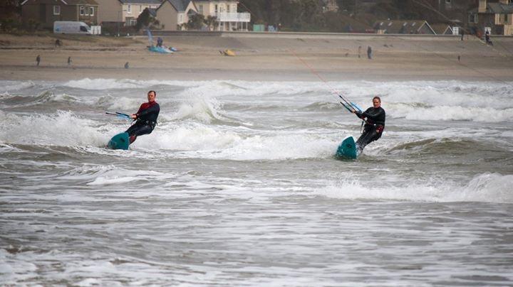 Two people kitesurfing